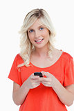 Woman beaming while sending a text with her cellphone