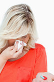 Young woman sneezing while holding some tablets