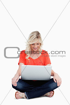 Attractive fair-haired woman sitting cross-legged with her hands