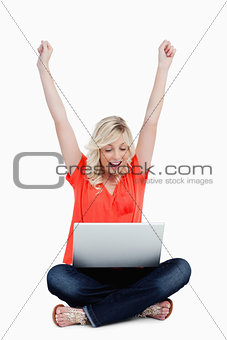 Young woman raising her arms in success in front of her laptop