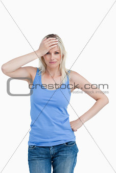 Blonde woman placing her hand on her forehead