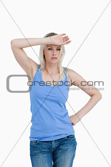 Sad blonde woman putting her hand on forehead