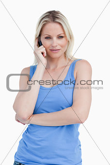 Blonde woman crossing her arms while calling