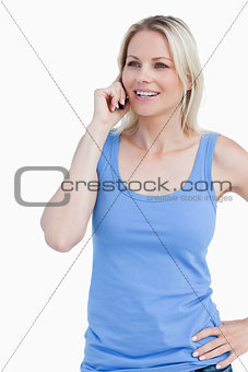 Smiling blonde woman using a mobile phone with a hand on her hip