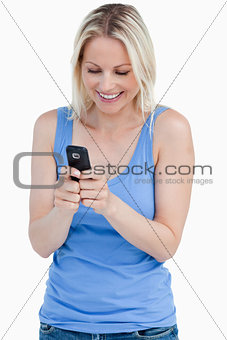 Smiling blonde woman sending a text with her cellphone