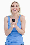 Blonde woman laughing while sending a text with her mobile phone