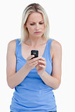 Serious woman looking at her mobile phone while concentrating
