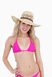 Smiling teenager wearing a pink swimsuit and a hat