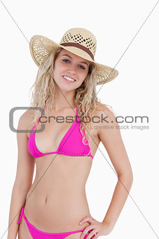 Smiling blonde teenager placing her left hand on her hip