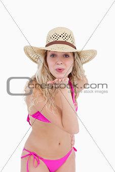 Attractive blonde teenager sending an air kiss