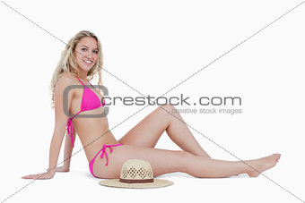 Smiling blonde teenager sitting on the floor next to her hat