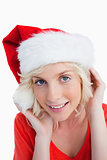 Young blonde woman putting on the Santa Claus hat