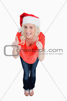 Fair-haired woman putting her thumbs up while wearing Christmas