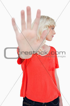Young woman making the stop sign with hand while leaning her hea