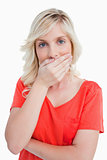 blonde woman covering her mouth with her hand