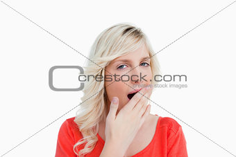 Young blonde woman yawning and covering her mouth with her hand