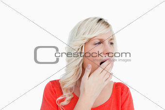 Young blonde woman looking on the side while yawning