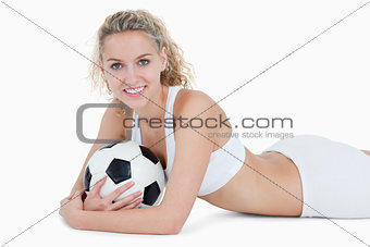 Smiling teenager lying down with a football in her arms