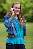 Young smiling and relaxed girl talking on the phone while standi