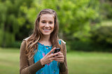 Smiling teenage using her cellphone while sending a text