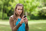 Teenage girl sending a text while looking at the camera