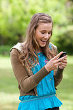 Happy teenage girl receiving a text on her cellphone while stand