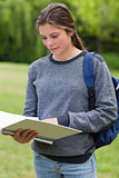 Young woman reading her notebook while standing up in a park