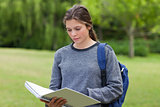 Young serious woman reading her notebook while standing in a par