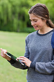 Young smiling woman touching her tablet pc while standing uprigh