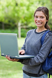 Smiling young girl holding her laptop while looking at the camer