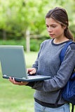 Serious student typing on her laptop while standing upright in a