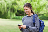 Smiling teenage girl using her cellphone while receiving a text