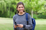 Young smiling woman looking at the camera while sending a text