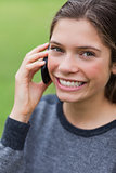 Teenage girl calling with her mobile phone while looking at the
