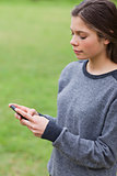 Young serious girl sending a text with her mobile phone