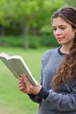 Young relaxed girl reading a book in a park