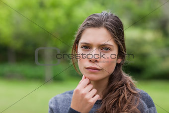 Thoughtful young girl placing her hand on chin while standing in