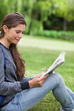 Young smiling woman reading a book while sitting on the grass in