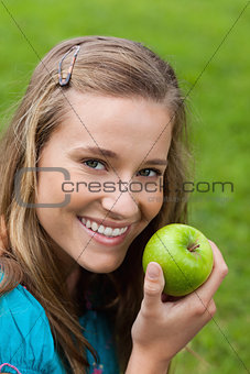 Attractive young girl eating a green apple in a park
