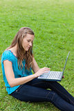 Young relaxed woman using her laptop while sitting on the grass