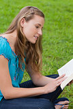 Young attractive girl sitting cross-legged in a park while readi
