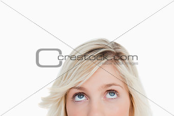 Upper part of the face of a blonde woman looking up