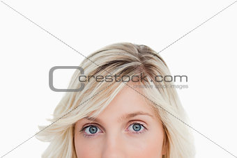 Upper part of a blonde woman's face looking straight at the came