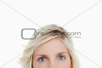 Upper part of a blonde woman face looking in front of her