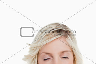 Woman closing her eyes while hiding the lower part of her face