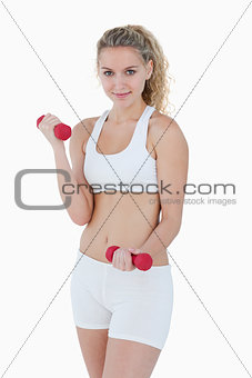 Young smiling woman lifting red weights