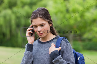 Thoughtful young girl using her mobile phone while carrying her