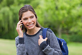 Young smiling girl looking away while talking on the phone