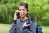 Young smiling girl talking on the phone while standing upright i