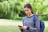 Young calm girl using her mobile phone to send a text